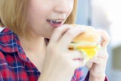 Het charmeren van mooie vrouw eet elke dag hamburger Hamburger stock afbeeldingen