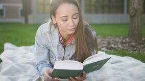 Het charmeren van mooie vrouw ligt op het gras en het lezen van intresting boek stock footage