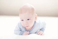 Het charmeren van pasgeboren babyjongen in blauw op een bed Royalty-vrije Stock Foto