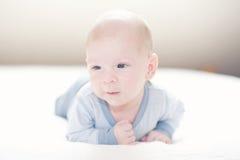Het charmeren van pasgeboren babyjongen in blauw op een bed Stock Fotografie
