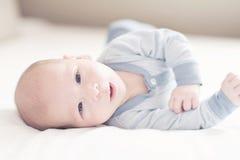Het charmeren van pasgeboren babyjongen in blauw op een bed Royalty-vrije Stock Foto's