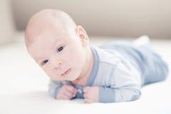 Het charmeren van pasgeboren babyjongen in blauw op een bed Royalty-vrije Stock Afbeeldingen
