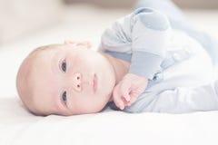 Het charmeren van pasgeboren babyjongen in blauw op een bed Royalty-vrije Stock Fotografie