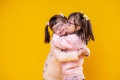 Het charmeren van positieve zusters die met chromosoomabnormaliteit elkaar koesteren royalty-vrije stock fotografie