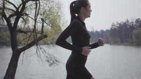 Het charmeren van slanke sporten jonge vrouw in sportkleding die op riverbank lopen Actieve levensstijl, sport De dame die haar h stock videobeelden