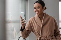 Het charmeren van vrolijke vrouw gebruikt haar smartphone royalty-vrije stock foto's