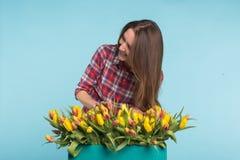 Het charmeren van vrouwelijke bloemist regelt tulpen in de doos, selecteert hen voor het toekomstige bloemstuk stock fotografie
