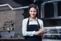 Het charmeren van vrouwelijke kelner in schort het schrijven orde royalty-vrije stock fotografie