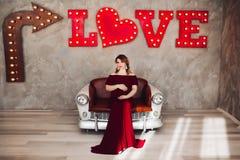 Het charmeren van zwangere vrouw in marsalakleding het stellen op stappen van huis royalty-vrije stock foto's
