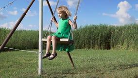 Het charmeren weinig blondemeisje slingert bij een groen gebied stock footage