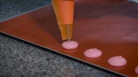 Het chef-kokgebakje begint het dienblad te vullen waarop bakseldocument voor baksel, roze room leg, die dan Macaron kan zijn stock footage