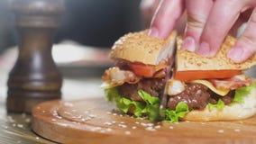 Het chef-kokmes snijdt Hamburger op een houten rond dienblad op de achtergrond van de keuken stock videobeelden