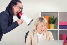 Het chef- schreeuwen bij werknemer op megafoon stock foto