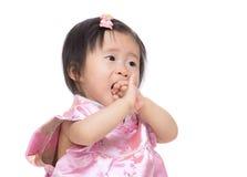Het Chinese babymeisje zuigt vinger in mond stock afbeelding