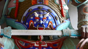 Het Chinese beeldhouwwerk die van immortals Boeddhistische Vajra een zwaard in gesneden stralen houden schilderde gebouwen, majes stock footage