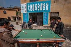 Het Chinese mensen speelbiljart bij binnenplaats bij oud dorp in het centrum, geniet van activiteit na het werk Yunnan, China stock foto