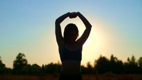 Het cijfer, overzicht van een mooi, atletisch meisje met lang blond haar, doet oefeningen, die zich bij zonsondergang, tegen uitr stock video