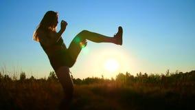 Het cijfer, overzicht van een mooi, atletisch meisje met lang blond haar, doet oefeningen, het in dozen doen, vliegende benen, di stock video