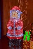 Het cijfer van een groot Russisch Nieuwjaar ` s Santa Claus verfraaide met multicolored fonkelende slingers Royalty-vrije Stock Foto