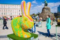 Het cijfer van een konijn of een haas onder het mom van het kameleon tegen de achtergrond van monument aan Bohdan Khmelnytskyi Mo stock foto