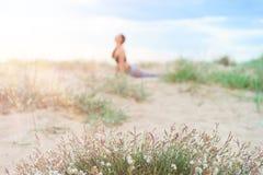 Het cijfer van een meisje vertroebelde op de achtergrond, uitoefenend yoga stock fotografie