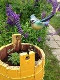 Het cijfer van een vogel met in een gele houten ton met bloemen Op de achtergrond zijn purpere lupines De decoratie van de tuin royalty-vrije stock fotografie