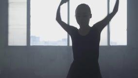 Het cijfer van professionele ballerina die in zwarte kleding in de studio voor een groot venster dansen Jonge mooi stock video