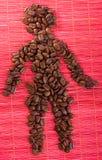 Het cijfervorm van de mens door koffiebonen op een mat Stock Fotografie
