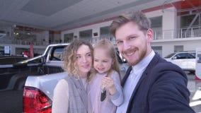 Het cliëntpaar met leuk kindmeisje met de video van het sleutelsverslag op mobiele telefoon dichtbij nieuwe gekochte auto in auto stock videobeelden