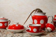 Het close-up één rat beklimt in rode theepot dichtbij rode koppen op countertop bij keuken in een flatgebouw royalty-vrije stock foto