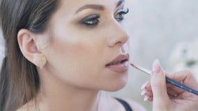Het close-up, bebouwd kader, de grimeur vraagt de cliënt glimlachen om de lippen met lippenstift goed te schilderen, toen stock videobeelden