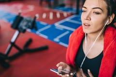 Het close-up bebouwde portret van een mooie sportieve jonge vrouw die aan muziek die van haar smartphone luisteren, een onderbrek stock afbeelding