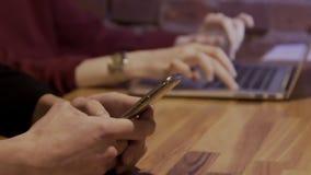 Het close-up bij lijstvrouw gebruikt een laptop en man types tekst op telefoon stock video