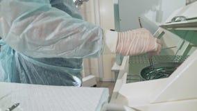 Het close-up, chirurg het werken in het ziekenhuis desinfecteert de medische instrumenten vóór de verrichting Arts in glazen stock footage