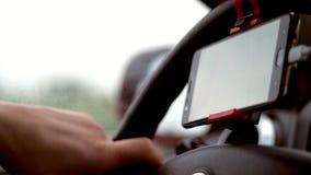 Het close-up, in de auto, de bestuurders` s hand houdt het stuurwiel van de auto, een gadget, mobiele telefoon, is de navigator stock videobeelden