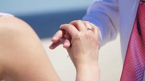 Het close-up, de bruid en de bruidegom dragen ringen aan elkaar, tegen de achtergrond van het overzees, het zand en de blauwe hem stock video