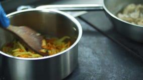 Het close-up, de kok bereidt verschillend voedsel op het fornuis voor hutspotvlees in een koekepan, Pan De professionele Chef-kok stock videobeelden