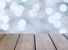 Het close-up de lege donkere bruine houten lijstbovenkant met lichtblauwe en witte Kerstmis defocused steekt bokeh achtergrond aa Royalty-vrije Stock Foto
