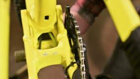 Het close-up in een fietsreparatiewerkplaats de meester verwijdert de pedalen voor onderhoud Fietsreparatie stock video