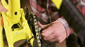 Het close-up in een fietsreparatiewerkplaats de meester verwijdert de pedalen voor onderhoud Fietsreparatie stock videobeelden