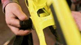 Het close-up in een fietsreparatiewerkplaats de meester verwijdert de pedalen voor onderhoud Fietsreparatie stock footage