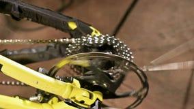 Het close-up in een fietsreparatiewerkplaats, een meester verwijdert een wiel voor onderhoud Fietsreparatie stock footage