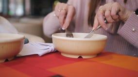 Het close-up een plaat van bollen in het restaurant, een meisje met een vork en mes eet de hete bollen stock video