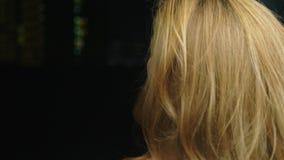 Het close-up, een vrouw raakt haar haar, tegen de achtergrond van de nachtstad Het concept van de haargezondheid stock video