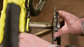 Het close-up in een workshop die fietsen herstellen de meester smeert de schacht van de pedaalassemblage voor onderhoud Fiets stock videobeelden