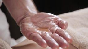 Het close-up giet olie in de palm Osteopaat die manipulatiemassage op vrouwelijke buik doen Mensenhanden die wijfje masseren stock video