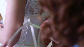 Het close-up, huwelijk, meisje helpt de bruid om de huwelijkskleding te kleden stock video