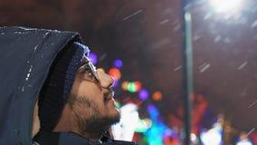 Het close-up, Indische kerel in glazen bekijkt vliegende sneeuw in de avond in het park stock footage