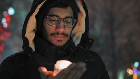 Het close-up, Indische mens in glazen bekijkt pensively ter beschikking een het branden kaarsholding stock videobeelden
