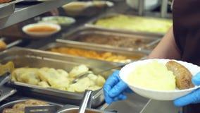 Het close-up, kantinearbeider legt een gedeelte fijngestampte aardappels op de plaat in moderne kantine, cafetaria, restaurant va stock videobeelden